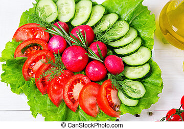 Coarsely chopped fresh cucumber, tomato, radish and lettuce - fresh salad. The concept of healthy eating, diet, vegetarianism