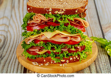 Colorful big sandwich with ham, cheese and vegetables.