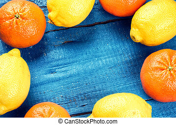 Colorful frame with citrus fruits - lemons and tangerines