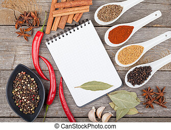 Colorful herbs and spices selection. Aromatic ingredients on wood table with blank notepad copyspace