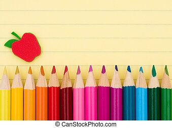 Colorful pencil crayons on a sheet of lined paper, Education background