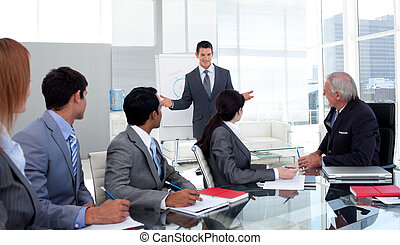 Confident businessman giving a presentation to his team in the office