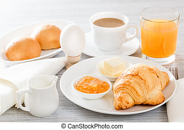 Continental breakfast with a croissant, boiled egg. Coffee or tea with milk, a glass of juice, buns, butter, jam