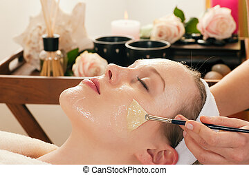 Woman having a mask or cream applied in the course of a beauty treatment