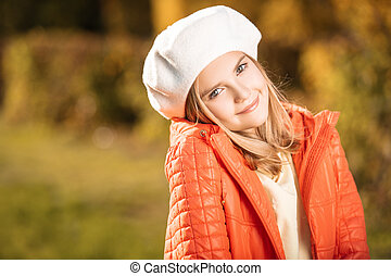 A cute fair-haired girl in clothes on autumn clothes countryside. Beauty, autumn fashion.