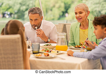 Grandparents and sister with brother having delicious breakfast