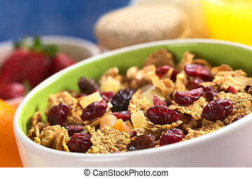 Delicious healthy breakfast with a bowl full of wholewheat flakes mixed with dried fruits (cranberries, bananas, raisins and some others) and nuts with fresh fruits, yogurt and orange juice around (Selective Focus, Focus one third into the bowl)