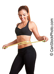 Woman measuring her waist with a yellow measuring tape, isolated in white