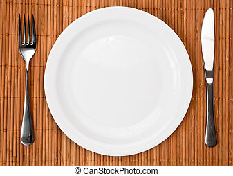 Knife, white plate and fork on bamboo mat