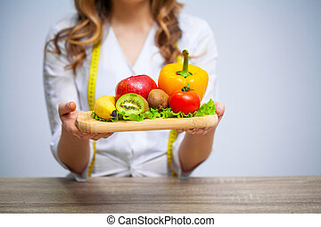 Doctor Nutritionist holding fresh fruits and vegetables for healthy diet.