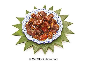 dried dates in ceramic bowl on banana leaf