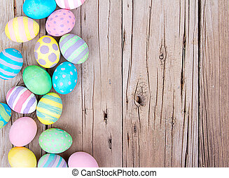 Easter eggs painted in pastel colors on a wooden background