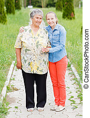 Elderly woman walk with her daughter in the park