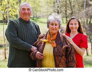 Photo of happy elderly couple and young caregiver
