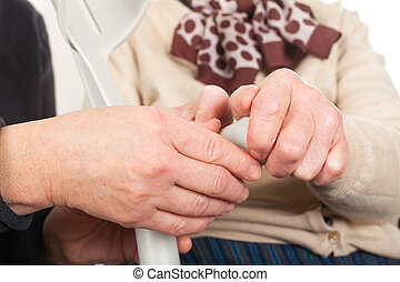 Elderly hands holding a crutch