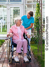 Elderly lady in a wheelchair with her carer taking an outing down a pathway in front of the care home pausing to chat and smile at each other