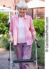 Elderly lady using a walker in the garden