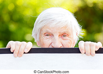 Portrait of the smiling elderly woman on outdoors