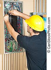 Electrician changing a breaker in a large industrial breaker panel.