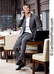 Happy business man speaks by a mobile phone at restaurant