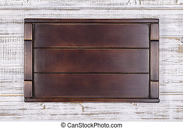 Empty dark wooden tray on gray background, close up