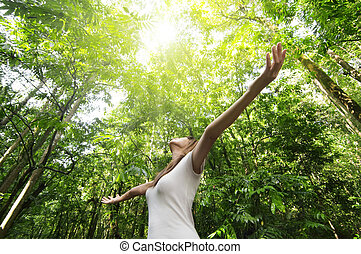 Young woman arms raised enjoying the fresh air in green forest