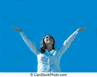 A hispanic woman with arms extended to the sky.