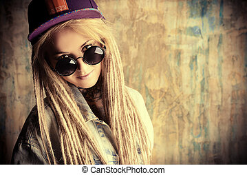 Modern teenage girl with blonde dreadlocks over grunge background. Jeans style. Modern generation.
