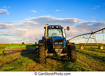 Farm equipment in the field with blue sky and clouds