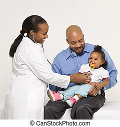 African-American female pediatrician examining baby girl being held by father.