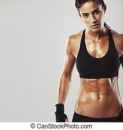 Picture of a fitness model on grey background. Young woman bodybuilder with muscular body looking at camera with copyspace