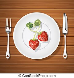 fork with knife and strawberries in heart shape on plate