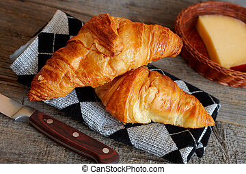 Original French croissants is a buttery flaky viennoiserie bread roll named for its distinctive crescent shape. Cheese in basket and knife as a background.