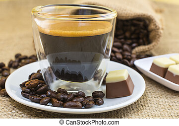 fresh espresso coffee with crema foam in a transparent cup and scattered coffee beans roasted