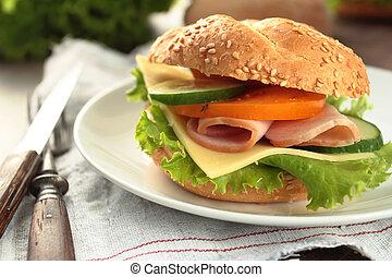 Fresh lettuce, tomato, cucumber, and ham in a sandwich