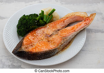 fried salmon trout with boiled vegetables on the dish