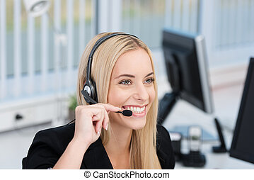 Friendly attractive young female call centre operator or receptionist wearing a headset and listening to the conversation with a lovely wide smile