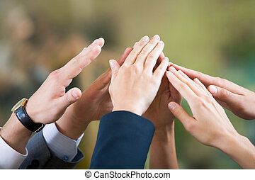 Close-up of several human hands making gesture of unity
