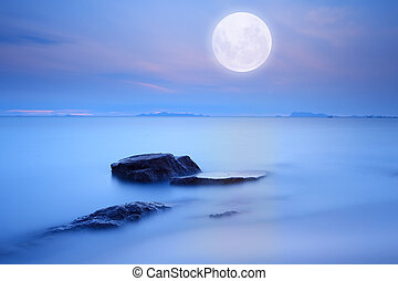 Full moon over blue sea and sky ,Long exposure technique