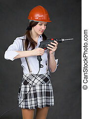 Girl in helmet standing on a black background with drill
