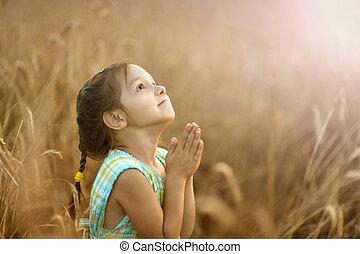 Girl prays in wheat field