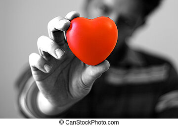 A young man giving is red hear with love (focus on the heart)