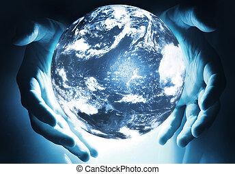 Glowing earth sphere in hands