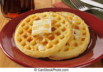 Hot buttered waffles with maple syrup on a rustic wooden table