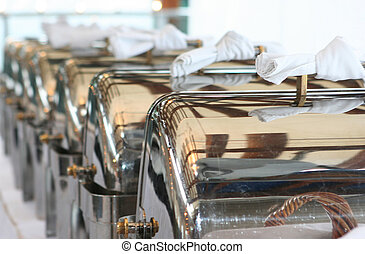 A line of silver serving trays blurring in the distance.