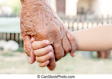 Grandchild holding grandparent for the hand, selective focus