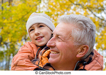 portrait of a grandfather with child at park