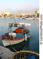 A Greek fishing caique (kaiki) with a long-line basket, hooks planted all round its rim, in the foreground. A common sight in the Greek islands, this was shot in Heraklion, Crete. The focus is on the boat.