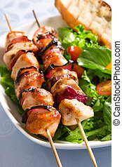 Grilled chicken onion skewers with salad and crouton