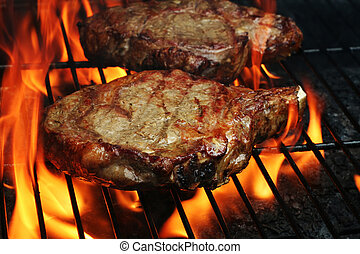 Two Juicy stakes grilling on the barbeque with lots of flame licking around them